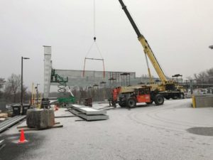 Solar canopy construction photo of rigging crew craning steel truss into place.